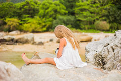 Offended sad girl with long hair sitting on a rock on the shore back Stock Photo