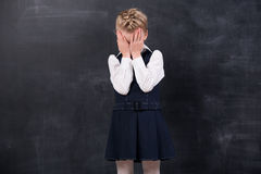 Offended Schoolgirl Stands At The Blackboard Royalty Free Stock Photos