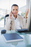 Offended sophisticated businesswoman on the phone. In bright office stock images