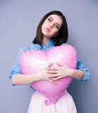 Offended young girl holding heart shaped balloon Stock Photo