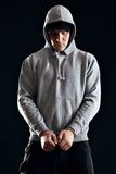 Offender Busted for His Crime. Handcuffed offender wearing a hooded sweatshirt stock photography