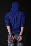 The offender in handcuffs. On a black background stock photos