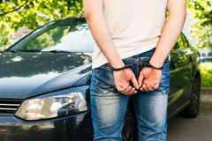 an offender standing in handcuffs near the car. Concept of arrest the driver, violation of rules and drinking alcohol while stock images