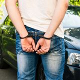 An offender standing in handcuffs near the car. Concept of arrest the driver, violation of rules and drinking alcohol while. Driving the car royalty free stock photo