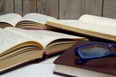 Offene alte Bücher und Gläser auf hölzernem Hintergrund stockfoto