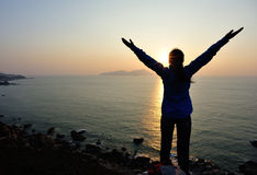 Offene Arme der dankbaren Frau zum Sonnenaufgang Lizenzfreie Stockfotografie