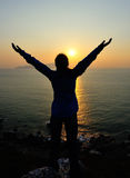 Offene Arme der dankbaren Frau zum Sonnenaufgang Stockfotografie