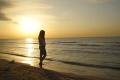 Offene Arme der Frau unter dem Sonnenaufgang an der Küste lizenzfreie stockfotografie
