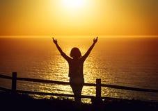 Offene Arme der glücklichen Frau unter dem Sonnenuntergang an der Küste lizenzfreies stockbild