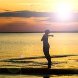 Offene Arme einer starken überzeugten Frau zum Sonnenuntergang stockfotos