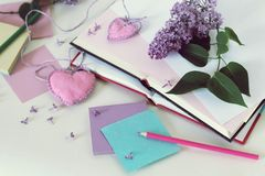 Offene B?cher, Bookmarkherzen, Papier, Bleistifte, Niederlassungen von lila Blumen auf dem Tisch stockfotos