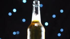 Offene Bierflaschenahaufnahme Helles Bier in der Flasche gedreht über schwarzen Hintergrund stock video footage