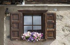 Offene Fensterläden des Fensters mit Blumen auf Fensterbrett Stockfotos