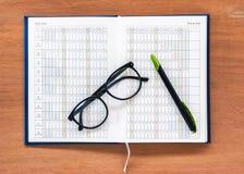 Offene Kalenderseite des Tagebuchplanerbuches mit Gläsern und Stift auf Th Lizenzfreies Stockbild