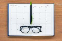 Offene Kalenderseite des Tagebuchplanerbuches mit Gläsern und Stift auf Th Stockfotos