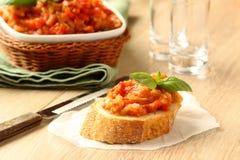 Offene Sandwiche mit Blättern des Auberginensalats (Kaviar) und -basilikums Lizenzfreie Stockfotos