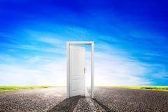 Offene Tür auf langer leerer Asphaltstraße in Richtung zur Sonne. Stockfotografie