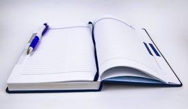 Offene Wochenzeitung mit Stift auf weißem Hintergrund stockfotografie