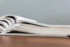 Offene Zeitschriften liegen auf einander auf einer braunen Tabelle, Dokumente sind Staplungsnahaufnahme stockfotografie