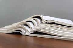 Offene Zeitschriften liegen auf einander auf einer braunen Tabelle, Dokumente sind Staplungsnahaufnahme lizenzfreie stockbilder