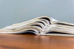 Offene Zeitschriften liegen auf einander auf einer braunen Tabelle, Dokumente sind Staplungsnahaufnahme lizenzfreie stockfotos