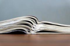 Offene Zeitschriften liegen auf einander auf einer braunen Tabelle, Dokumente sind Staplungsnahaufnahme stockbild