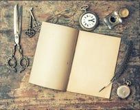 Offene Zeitschriftenbuch- und Weinleseschreibenswerkzeuge auf Holztisch stockfoto