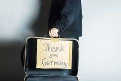 Offener Koffer des Flüchtlings mit Mitteilung danken Ihnen Deutschland auf cardb Lizenzfreie Stockfotos