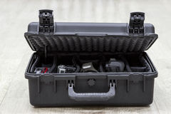 Offener Kunststoffkoffer des Stückchen auf Boden mit Fotoausrüstung in den Teilern Stockbild