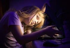 Offener Laptop und Blicke des kleinen Mädchens nach innen Stockfotografie