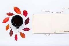 Offener Notizblock mit fallenden Blättern und Tasse Kaffee des Herbstes Lizenzfreies Stockbild