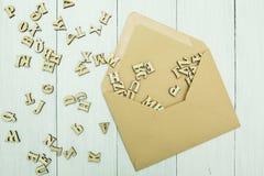 Offener Papierpostumschlag mit zerstreuten hölzernen Buchstaben nach innen auf einer weißen Tabelle stockbilder
