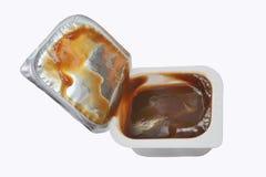 Offener Plastikbehälter mit Soßenketschup oder ein Grill lokalisiert auf einem weißen Hintergrund stockbild