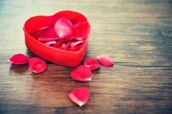 Offener roter Herzkasten des Valentinsgrußtagesliebesherzkonzeptes verziert mit den Blumenblättern der roten Rosen auf hölzernem lizenzfreies stockbild