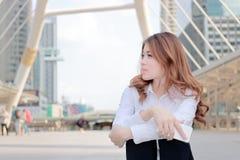 Offener Schuss der attraktiven jungen asiatischen Geschäftsfrau, die über etwas am Stadthintergrund denkt und träumt Stockfoto