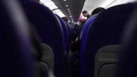 Offener Schuss zwischen Sitzen von den Passagieren, die innerhalb des Flugzeuges beim Reisen sitzen stock video footage