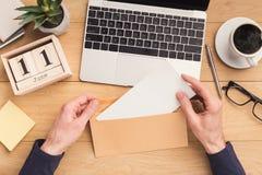 Offener Umschlag des Mannes am Arbeitsplatz beim Arbeiten Lizenzfreies Stockfoto
