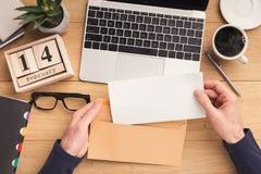Offener Umschlag des Mannes am Arbeitsplatz beim Arbeiten Lizenzfreies Stockbild