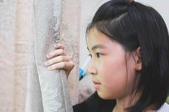 Offener Vorhang des Mädchens, der draußen mit abwesendem gekümmert schaut Stockfoto