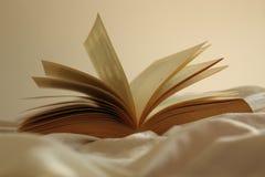 Offenes altes Buch auf einem Bett lizenzfreies stockbild