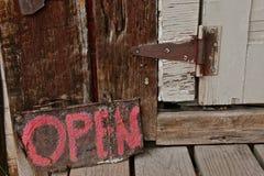 OFFENES altes hölzernes Zeichen durch eine rustikale Schalentür mit einem rostigen Scharnier lizenzfreie stockfotos