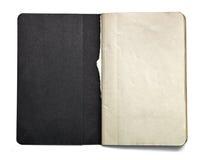 Offenes Anmerkungsbuch des freien Raumes mit dem schwarzen Titelblatt lokalisiert auf weißem Hintergrund Lizenzfreie Stockfotografie