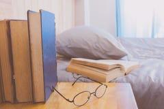 Offenes Buch auf Bett mit Reihenbuch- und Augenglasvordergrund Lizenzfreie Stockfotos