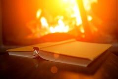 Offenes Buch auf dem Hintergrund eines brennenden Kamins stockfotografie