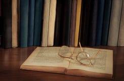 Offenes Buch auf dem Tisch, Gläser Stockfoto