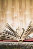 Offenes Buch auf einem Holztisch Lizenzfreie Stockfotos