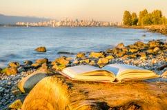 Offenes Buch auf einem Strand bei Sonnenuntergang Lizenzfreie Stockfotografie