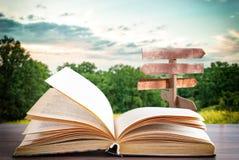 Offenes Buch auf einer Holzoberfläche und ein Zeiger im Hintergrund stockfoto