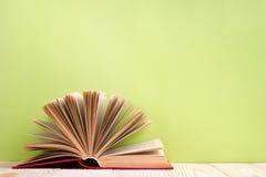 Offenes Buch auf grünem hölzernem Hintergrund Scheren und Bleistifte auf dem Hintergrund des Kraftpapiers Lizenzfreie Stockfotos