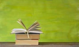 Offenes Buch auf grünem Hintergrund, Freiexemplarraum Stockfotos